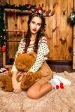 Mädchen mit Bären in ihrer Hand, die im Raum mit hölzernen Wänden sitzt Stockfotos