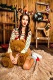 Mädchen mit Bären in ihrer Hand, die im Raum mit hölzernen Wänden sitzt Lizenzfreie Stockfotos