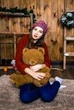 Mädchen mit Bären in ihrer Hand, die im Raum mit hölzernen Wänden sitzt Stockbild