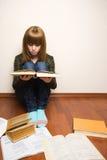 Mädchen mit Büchern auf dem Fußboden Stockbild