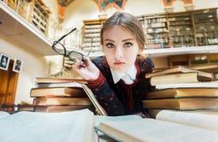Mädchen mit Büchern in der Bibliothek Stockbild