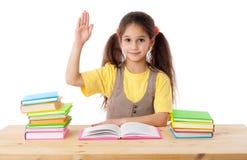 Mädchen mit Büchern und Erhöhungen seine Hand oben Lizenzfreie Stockbilder