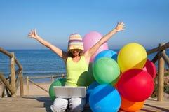 Mädchen mit Ballonen unter Verwendung eines Laptops lizenzfreie stockfotos