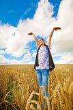 Mädchen mit beiden Armen oben im Himmel, der auf dem Weizengebiet steht stockfotografie