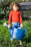 Mädchen mit Bewässerungsdose auf dem Gemüsegarten Stockfotos