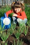 Mädchen mit Bewässerungsdose sitzt nahe Zwiebelenänderung am objektprogramm Stockfotografie