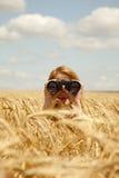 Mädchen mit binokularem am Weizenfeld. stockbild