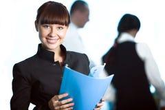 Mädchen mit blauem Faltblatt und Männer und Frauen Stockfoto