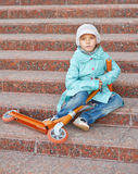 Mädchen mit blauem Mantel mit Roller Stockbilder