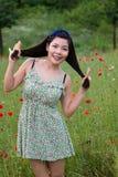 Mädchen mit blauer Band spielt mit ihrem Haar auf dem Mohnblumengebiet stockbild