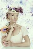 Mädchen mit Blumen auf dem Hut und der Hand unter dem Kinn Stockbilder