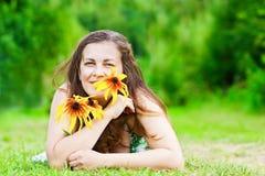 Mädchen mit Blumen legt in Park lizenzfreies stockfoto