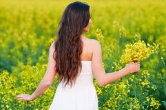Mädchen mit Blumen am Sommerfeld lizenzfreies stockbild