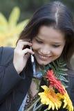 Mädchen mit Blumen sprechend durch Telefon Stockfoto