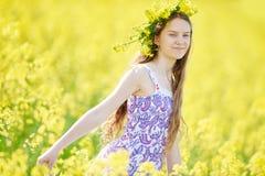 Mädchen mit Blumengirlande an der gelben Rapssamenwiese Lizenzfreies Stockbild