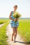 Mädchen mit Blumenstrauß von camomiles Stockfotografie
