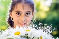 Mädchen mit Blumenstrauß von Gänseblümchen stockfoto