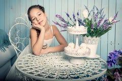 Mädchen mit Bonbons auf dem Tisch Lizenzfreies Stockbild