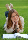 Mädchen mit Buch auf Gras Stockfotos