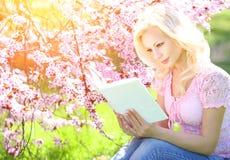Mädchen mit Buch Blonde junge Frau und Cherry Blossom Lizenzfreie Stockbilder