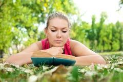 Mädchen mit Buch im Park Stockbilder