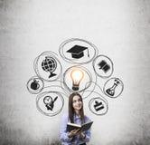 Mädchen mit Buch und Studienskizze auf Betonmauer Stockfotografie