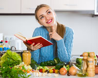 Mädchen mit Buch von Rezepten an der Küche Stockbild