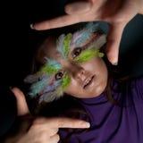 Mädchen mit bunter Feder auf ihrem Gesicht Stockbild