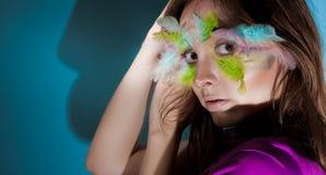 Mädchen mit bunter Feder auf ihrem Gesicht Stockfotografie