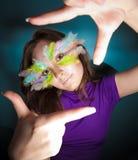 Mädchen mit bunter Feder auf ihrem Gesicht Lizenzfreie Stockfotos