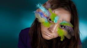 Mädchen mit bunter Feder auf ihrem Gesicht Stockfoto