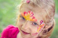Mädchen mit bunter Gesichtmalerei Stockbilder