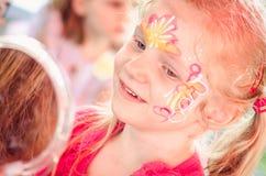 Mädchen mit bunter Gesichtmalerei Stockfotografie