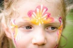 Mädchen mit bunter Gesichtmalerei Stockfotos