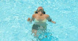 Mädchen mit dem Afro-Haarschnitt, der im Swimmingpool sich entspannt stock video footage