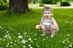 Mädchen mit dem Apfel, der auf dem Gras sitzt Lizenzfreie Stockfotos