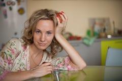 Mädchen mit dem Apfel, der am Tisch sitzt Lizenzfreie Stockfotografie