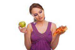 Mädchen mit dem Apfel und Pizza, die eine Entscheidung treffen Lizenzfreie Stockfotos