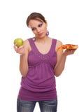 Mädchen mit dem Apfel und Pizza, die eine Entscheidung treffen Stockfoto