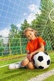 Mädchen mit dem Arm auf Fußball sitzt nahe Holzarbeit Stockfotografie