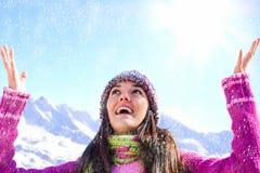 Mädchen mit dem Beanie, der mit Schnee spielt. Stockfotos