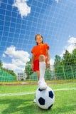 Mädchen mit dem Bein auf Fußball vor Holzarbeit Stockbild