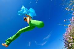 Mädchen mit dem blauem silk Schalspringen Stockfotos