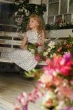 Mädchen mit dem blonden gelockten Haar auf einer Bank mit Blumen Lizenzfreies Stockfoto