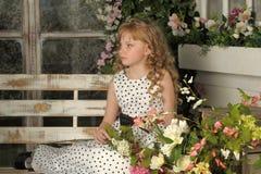 Mädchen mit dem blonden gelockten Haar auf einer Bank mit Blumen Lizenzfreie Stockfotografie