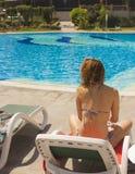 Mädchen mit dem blonden Haar, das auf einem Ruhesessel durch das Pool sitzt stockfotos