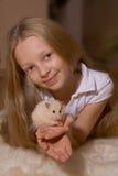 Mädchen mit dem blonden Haar, das einen Hamster anhält Stockfoto