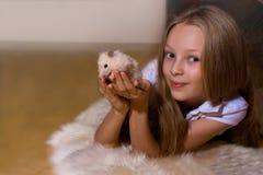 Mädchen mit dem blonden Haar, das einen Hamster anhält Stockbilder