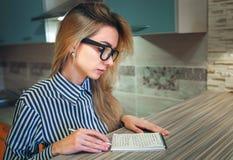 Mädchen mit dem blonden Haar, das zu Hause sitzt und das Papiernotizbuch betrachtet Lizenzfreie Stockbilder