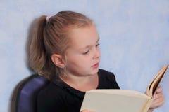 Mädchen mit dem blonden Haar ein Buch lesend Stockfotografie